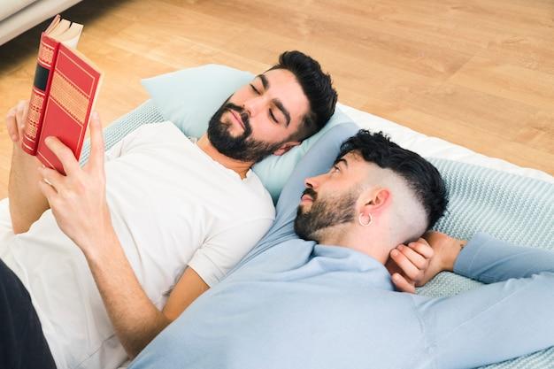 Mens die op bed ligt dat haar vriend bekijkt die het boek leest