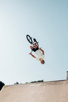 Mens die op bmxfiets sprong in skatepark uitvoert