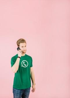 Mens die op cellphone tegen roze achtergrond spreekt