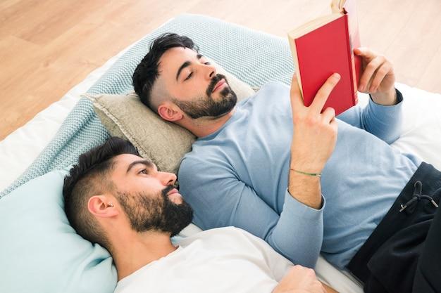 Mens die op comfortabel bed ligt dat zijn vriend bekijkt die het boek leest