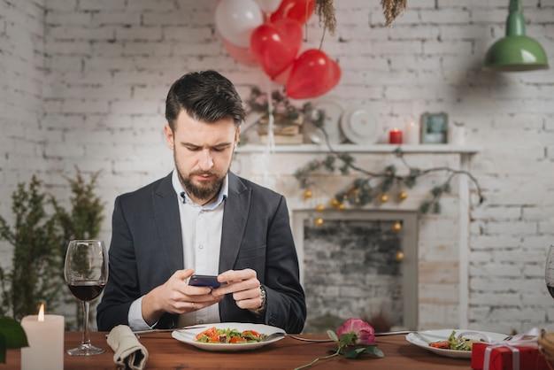 Mens die op datum wacht die telefoon controleert
