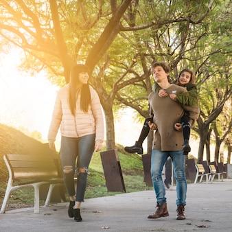 Mens die op de rug aan dochter geeft die in park met zijn vrouw loopt