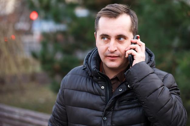 Mens die op de telefoon in de stad spreekt.