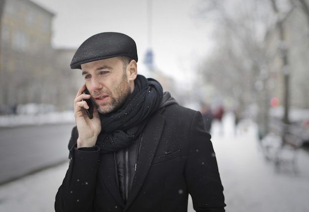 Mens die op de telefoon in de winter spreekt