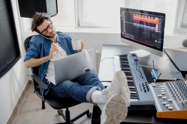 Mens die op de telefoon spreekt en aan laptop in de studio werkt