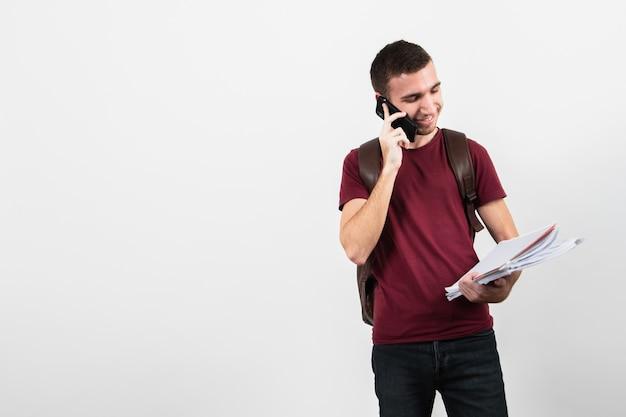Mens die op de telefoon spreekt en zijn nota's bekijkt