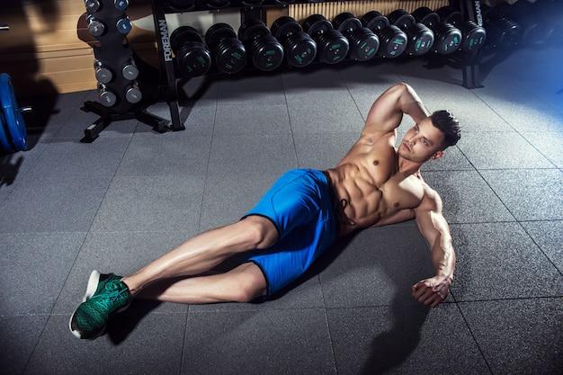 Mens die op de vloer in de gymnastiek vóór sterkteoefeningen opwarmen