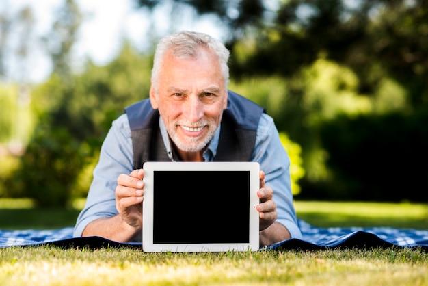 Mens die op een deken met een tabletmodel legt