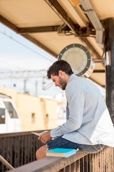 Mens die op een kaart kijkt en op trein wacht