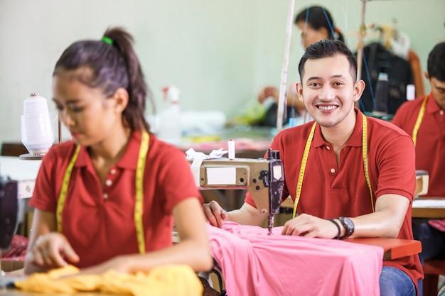 Mens die op een sewinghine naait en bij een kledingsfabriek glimlacht