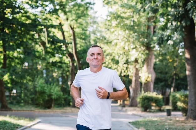 Mens die op een steeg in het park loopt