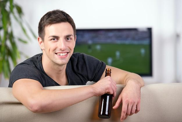 Mens die op een voetbalspel op bank met een bier let.