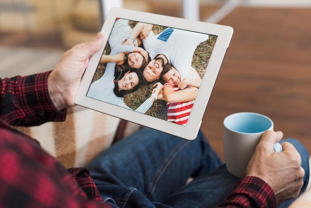 Mens die op foto's met zijn kinderen en kleinkinderen kijkt