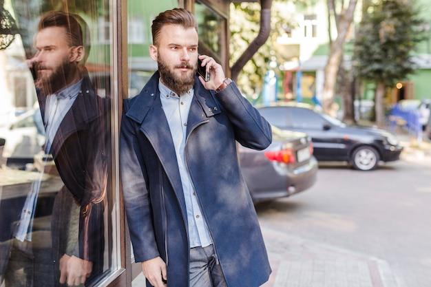 Mens die op glasvenster leunt dat op cellphone spreekt
