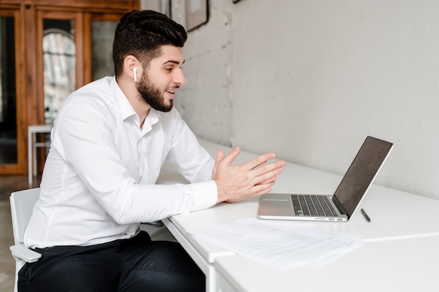 Mens die op laptop met draadloze earpods in het bureau communiceert