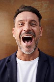 Mens die op middelbare leeftijd een jasje gelukkig lachen dragen
