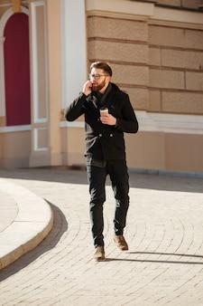 Mens die op mobiele telefoon spreekt en koffie in stad drinkt