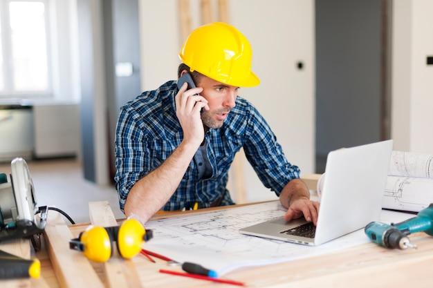 Mens die op mobiele telefoon spreekt en laptop aan bouwkant gebruikt