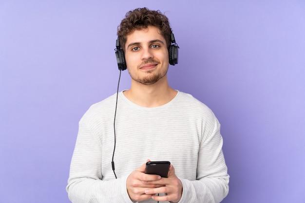 Mens die op purpere muur het luisteren muziek met mobiel wordt geïsoleerd en voorzijde kijkt