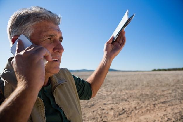 Mens die op telefoon spreekt terwijl status op landschap