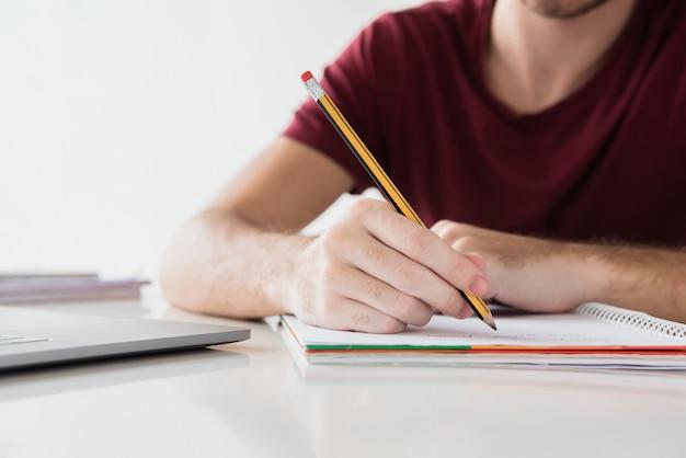 Mens die op zijn blocnote met potlood schrijft
