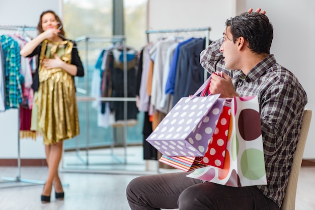 Mens die op zijn vrouw tijdens kerstmis het winkelen wacht