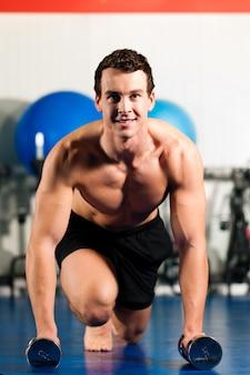 Mens die opdrukoefeningen in gymnastiek doet