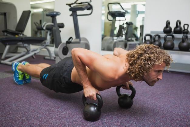 Mens die opdrukoefeningen met ketelklokken in gymnastiek doet