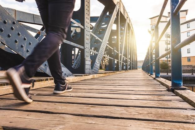 Mens die over een brug bij zonsondergang loopt