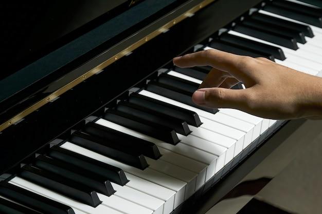 Mens die piano in de studio met vage hand speelt