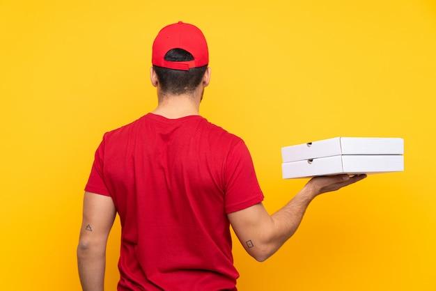 Mens die pizzadozen over geïsoleerde muur vangt