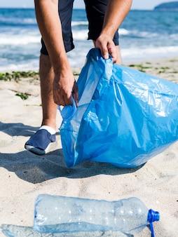 Mens die plastic afval van het strand verzamelt en het in blauwe vuilniszakken voor recycleert zet