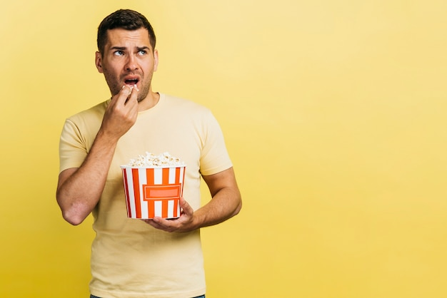 Mens die popcorn met exemplaarruimte eet
