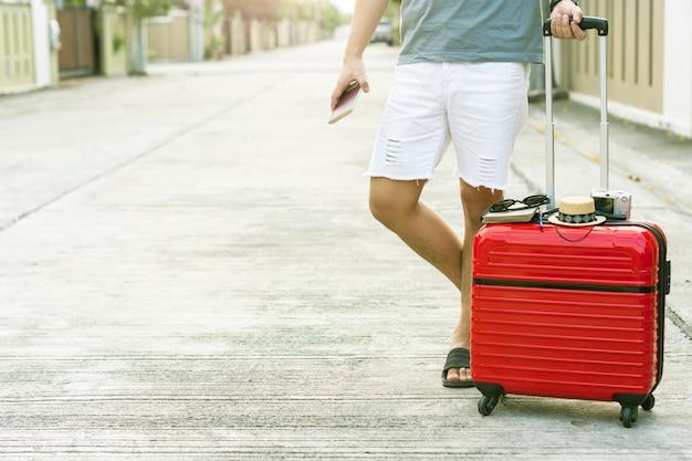 Mens die rode bagage met paspoort op vage stadsachtergrond houdt