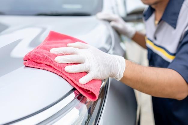 Mens die rode doek gebruikt om suv-auto schoon te maken