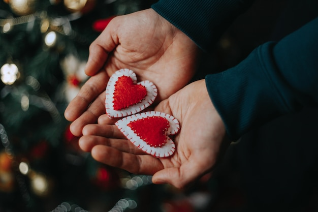 Mens die rode hart huidige doos in zijn handen met de decoratie van de kerstmisboom houden