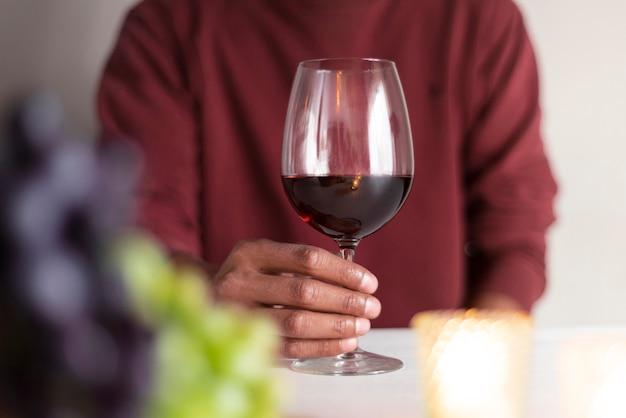 Mens die rood glas wijn houdt