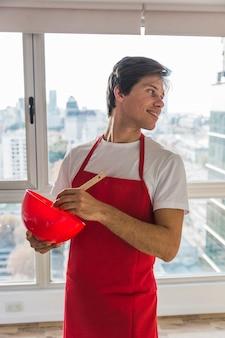 Mens die rood schort kokend voedsel draagt