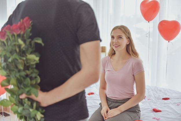 Mens die roze bloem geeft aan meisje voor de dag van valentine