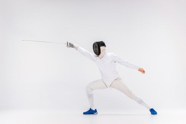 Mens die schermend kostuum het praktizeren met zwaard dragen tegen grijs
