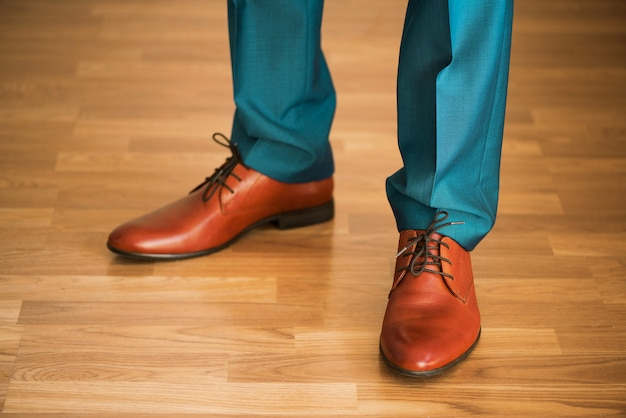 Mens die schoenen op houten vloer draagt. kledingsconcept, bruidegom die klaar vóór ceremonie worden. lichaamsdetail van zakenman.