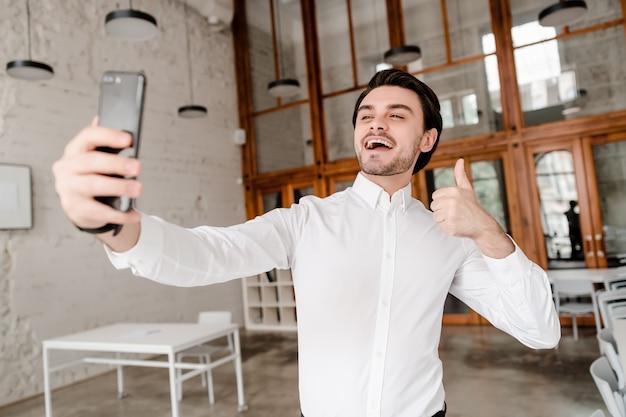 Mens die selfie met duimen omhoog op zijn telefoon maken