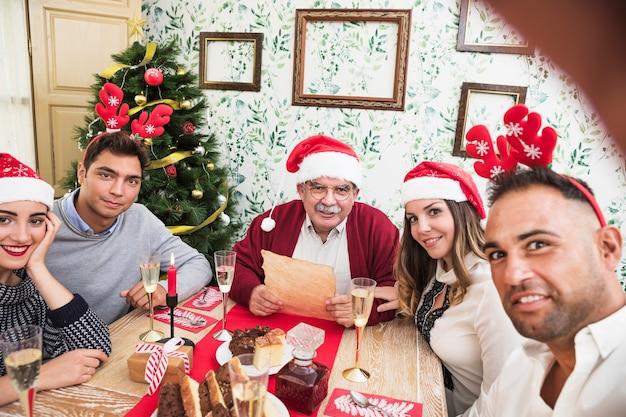 Mens die selfie met familie bij feestelijke lijst nemen