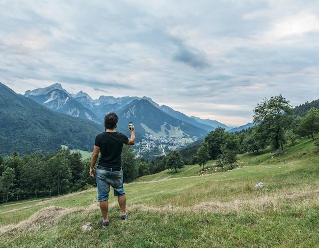 Mens die selfie op bergenlandschap nemen