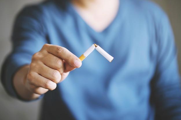 Mens die sigarettenconcept voor het ophouden met het roken en gezonde levensstijl weigeren.