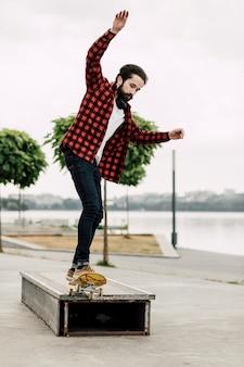 Mens die skateboardtrucs op een bank doet