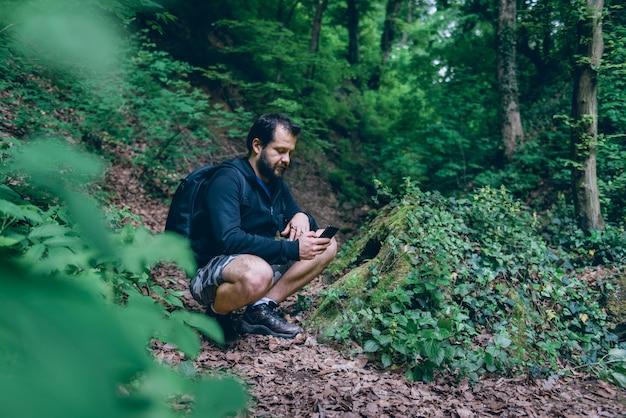 Mens die slimme telefoon met behulp van om in het bos te navigeren
