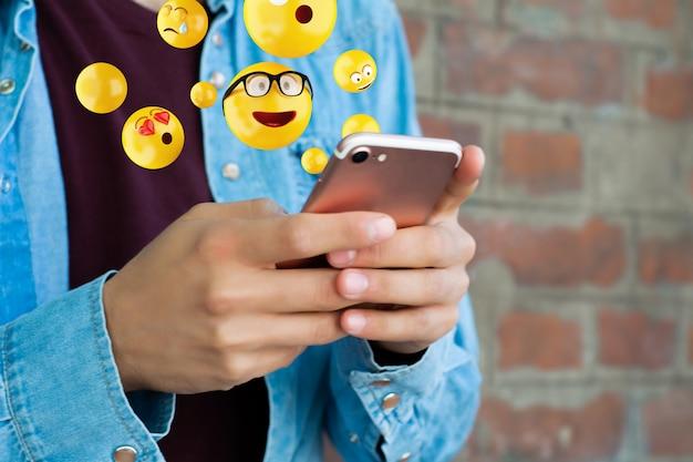 Mens die smartphone gebruikt die emoji's verzendt