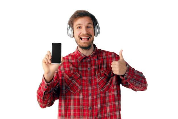 Mens die smartphone met behulp van die op witte studiomuur wordt geïsoleerd