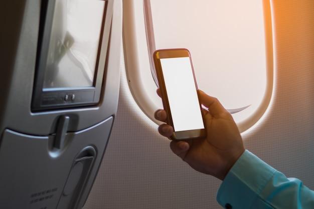 Mens die smartphone met het lege scherm op een vliegtuig dichtbij venster gebruiken